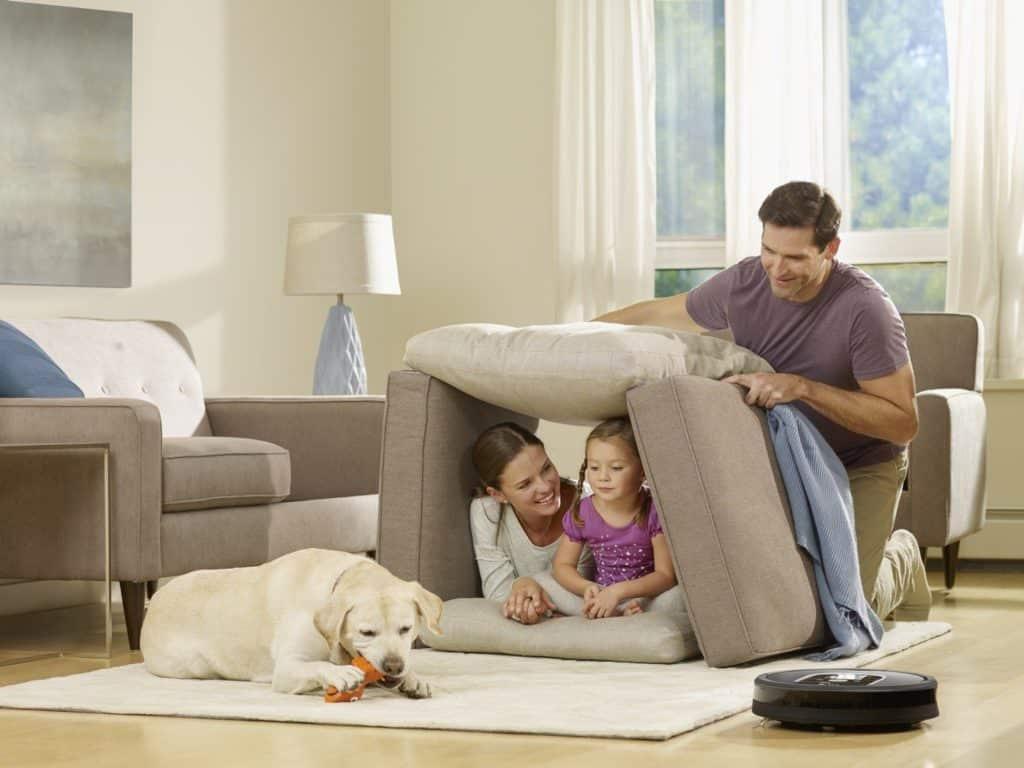 Une famille tranquil en train de se reposer pendant que leur aspirateur robot fait le travail et nettoye la maison en profondeur