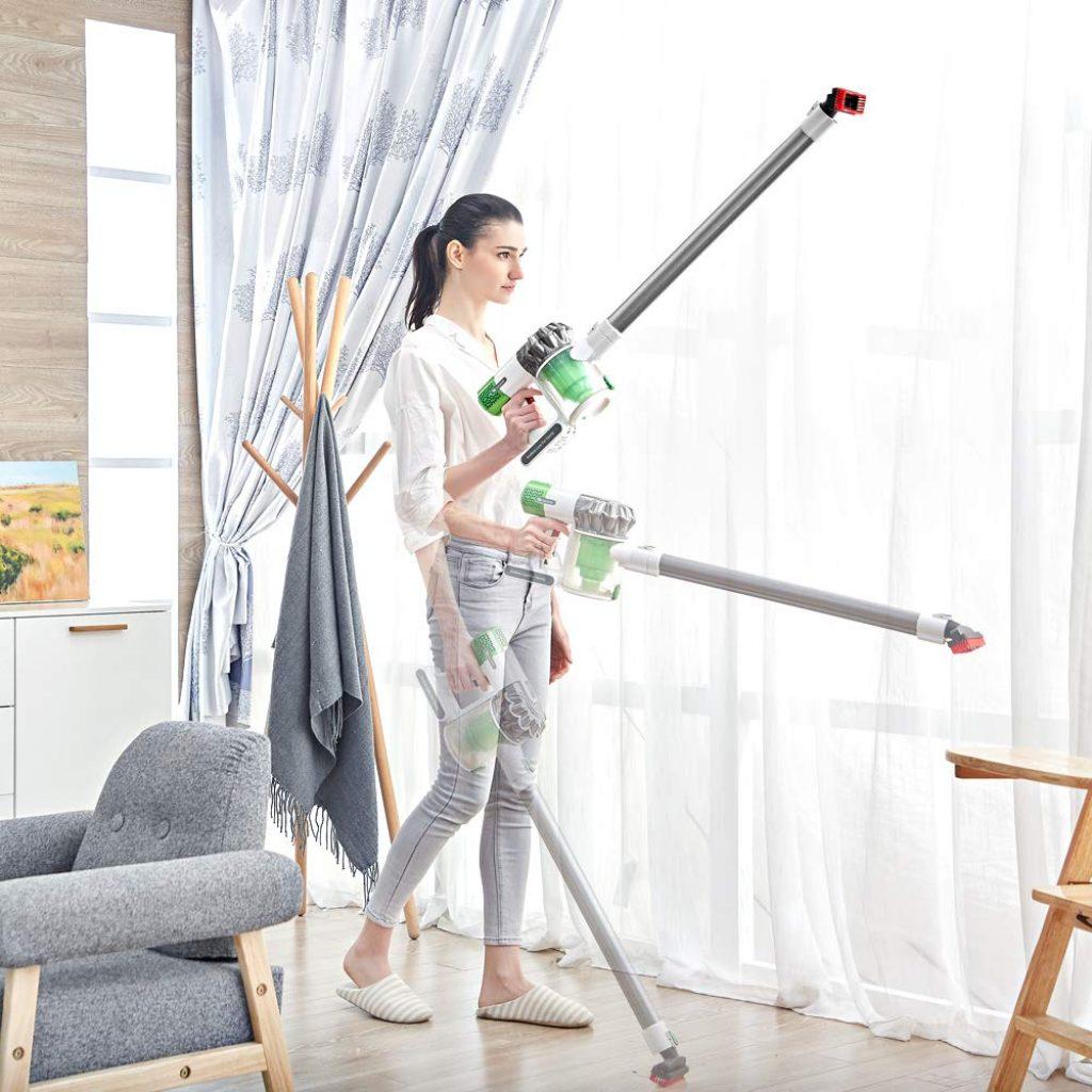 Une femme qui nettoie des rideaux avec son aspirateur Proscenic P9, son marie doit apprécier